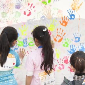 絵の具を付けた手でハイタッチをして地球の形のアートをつくる『地球にハイタッチ』。メッセージを添えて、支援先の子どもたちへ届けました。